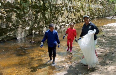 A Dad and two kids sweeping the creek of litter.