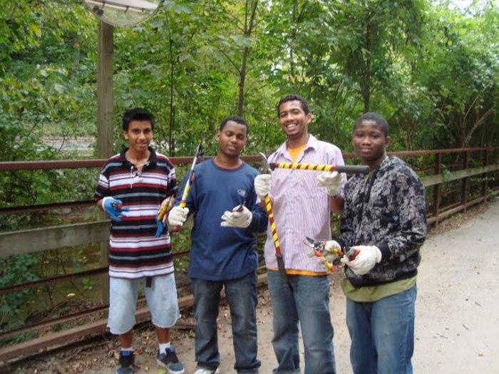 4 boys with tools to remove invasive plants