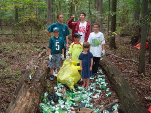 A group of volunteers getting ready to pick up a large pile of aluminum cans between two logs.