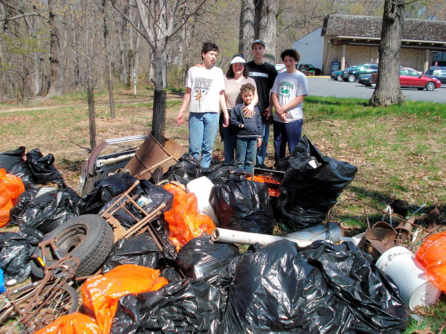 A family surveys the bags of trash collected at the Spring 2018 Sweep the Creek event