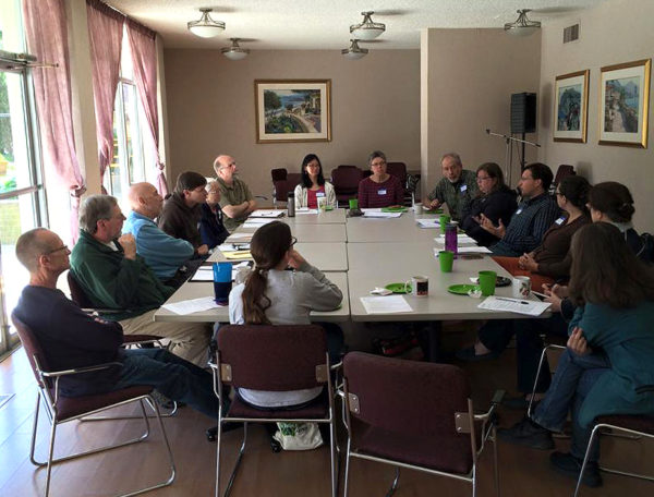 The FOSC Roundtable meeting around a large table in a bright conference room with windows along one side..